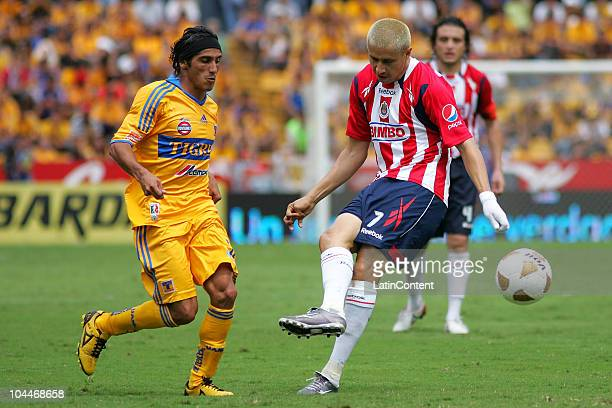 Damian Alvarez of Tigres struggles for the ball with Adolfo Bautista of Chivas during a match as part of the Apertura 2010 at Universitario Stadium...