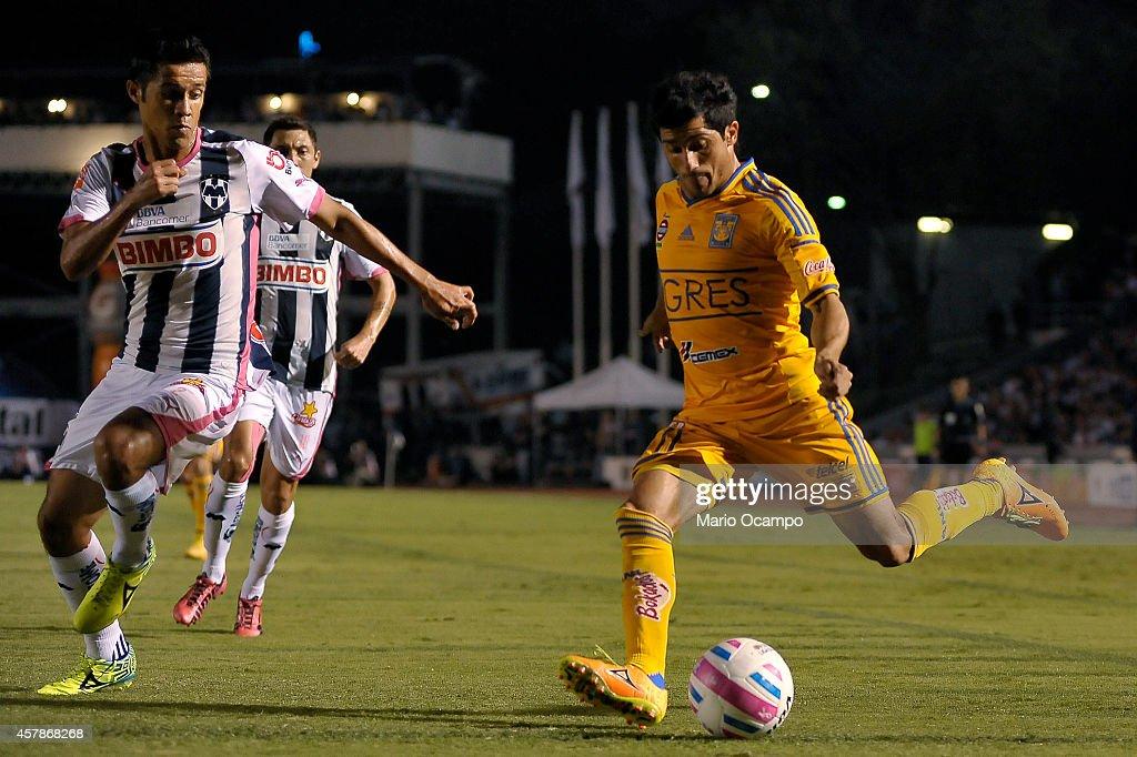 Damian Alvarez of Tigres tries to pass the ball followed as Severo Meza of Monterrey tries to block it during a match between Monterrey and Tigres...
