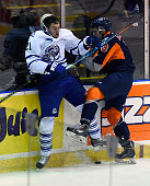 Damian Bourne of the Mississauga Steelheads and Alex Di Carlo of the Flint Firebirds crash the boards during OHL game action on October 4 2015 at the...