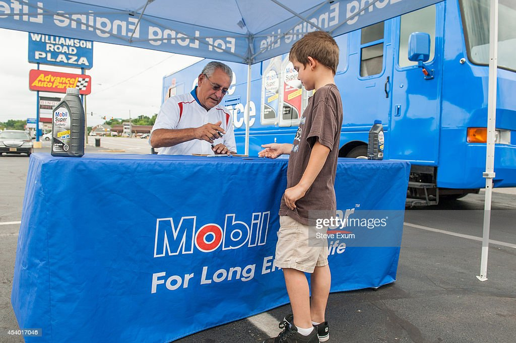 Damian Burk (6) watches former Major League pitcher and 1977 World Series Champion Mike Torrez, left, signs his collectible baseball cards at the Mobil Super 'Go the Distance' Baseball Tour bus August 23, 2014 at Advance Auto Parts in Roanoke, Virginia. Torrez joined the Mobil Super team to help change oil, meet fans and give away autographed baseballs and other prizes.