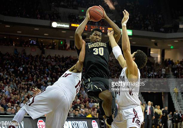 Damian Jones of the Vanderbilt Commodores battles PJ Dozier and Michael Carrera of the South Carolina Gamecocks for a rebound during their game at...