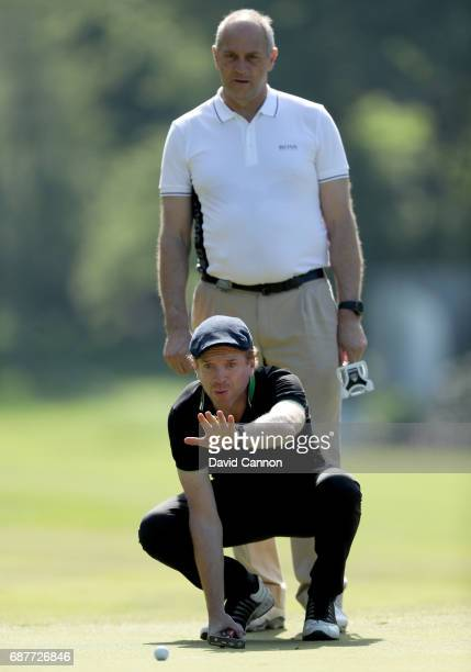 Damian Lewis of England the film television and stage actor waits lines up a putt watched by Sir Steve Redgrave the British rowing Olympian during...