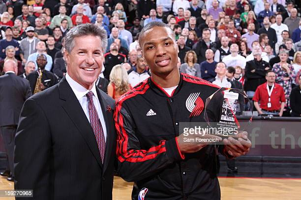 Damian Lillard of the Portland Trail Blazers accepts an award with Neil Olshey the General Manager of the Portland Trail Blazers prior to the game...