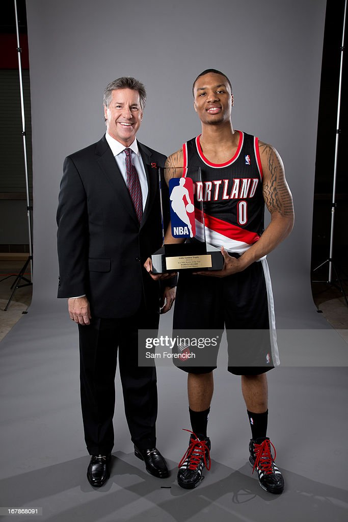 Damian Lillard #0 of the Portland Trail Blazers and Neil Olshey, the team's general manager, pose with the Eddie Gottlieb Trophy after Lillard won the 2012-2013 Kia NBA Rookie of the Year award on May 1, 2013 at the Rose Garden Arena in Portland, Oregon.