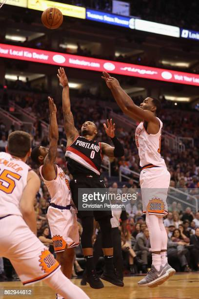 Damian Lillard of the Portland Trail Blazers attempts a shot over Tyler Ulis and TJ Warren of the Phoenix Suns during the second half of the NBA game...