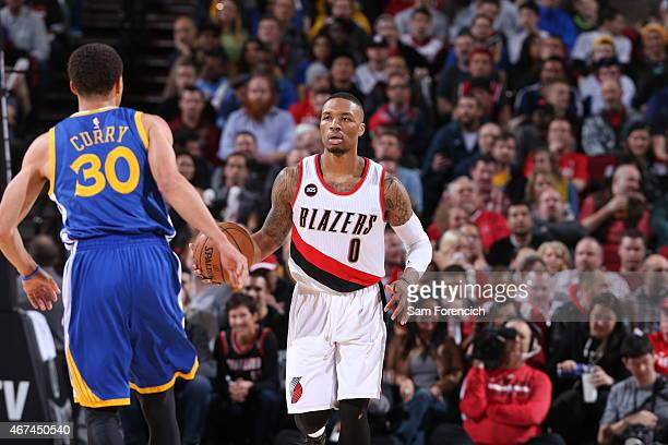 Damian Lillard of the Portland Trail Blazers brings the ball up court against Stephen Curry of the Golden State Warriors on March 24 2015 at the Moda...