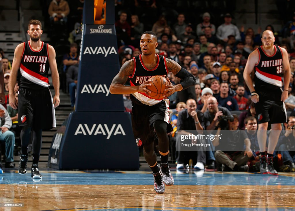 Damian Lillard of the Portland Trail Blazers controls the ball against the Denver Nuggets as Joel Freeland and Chris Kaman of the Portland Trail...