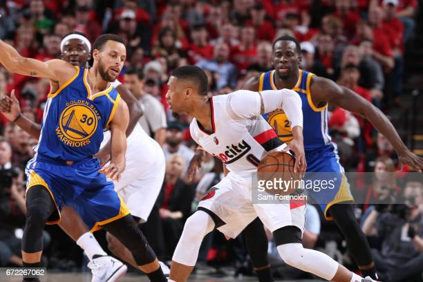 Damian Lillard of the Portland Trail Blazers dribbles the ball while guarded by Stephen Curry of the Golden State Warriors in Game Three of the...