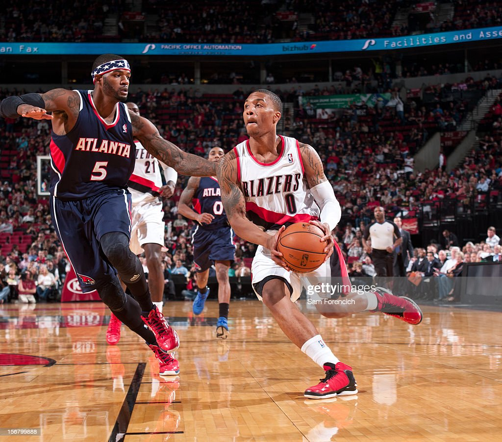 <a gi-track='captionPersonalityLinkClicked' href=/galleries/search?phrase=Damian+Lillard&family=editorial&specificpeople=6598327 ng-click='$event.stopPropagation()'>Damian Lillard</a> #0 of the Portland Trail Blazers drives to the basket against <a gi-track='captionPersonalityLinkClicked' href=/galleries/search?phrase=Josh+Smith+-+Basketball+Player+-+Born+1985&family=editorial&specificpeople=201983 ng-click='$event.stopPropagation()'>Josh Smith</a> #5 of the Atlanta Hawks on November 12, 2012 at the Rose Garden Arena in Portland, Oregon.