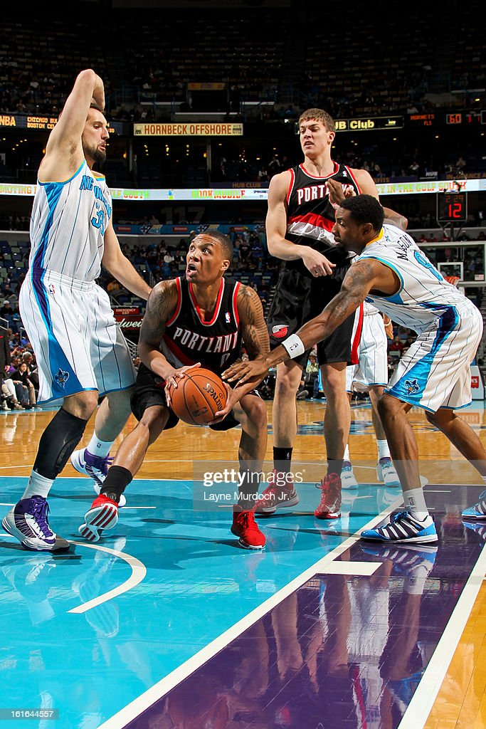 <a gi-track='captionPersonalityLinkClicked' href=/galleries/search?phrase=Damian+Lillard&family=editorial&specificpeople=6598327 ng-click='$event.stopPropagation()'>Damian Lillard</a> #0 of the Portland Trail Blazers drives to the basket against Ryan Anderson #33 and <a gi-track='captionPersonalityLinkClicked' href=/galleries/search?phrase=Roger+Mason+Jr.&family=editorial&specificpeople=220399 ng-click='$event.stopPropagation()'>Roger Mason Jr.</a> #8 of the New Orleans Hornets on February 13, 2013 at the New Orleans Arena in New Orleans, Louisiana.