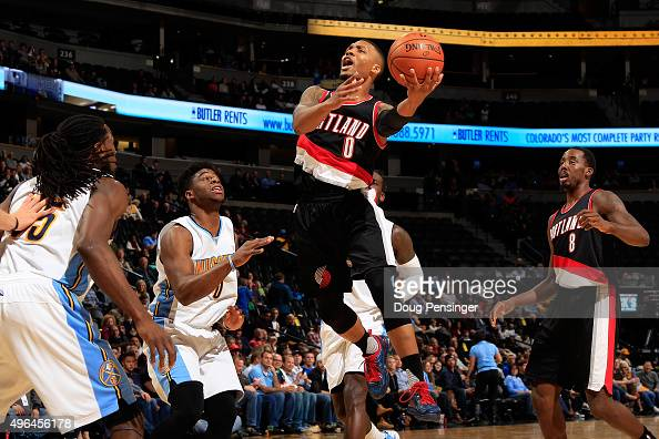 Damian Lillard of the Portland Trail Blazers drives to the basket against Emmanuel Mudiay and Kenneth Faried of the Denver Nuggets at Pepsi Center on...