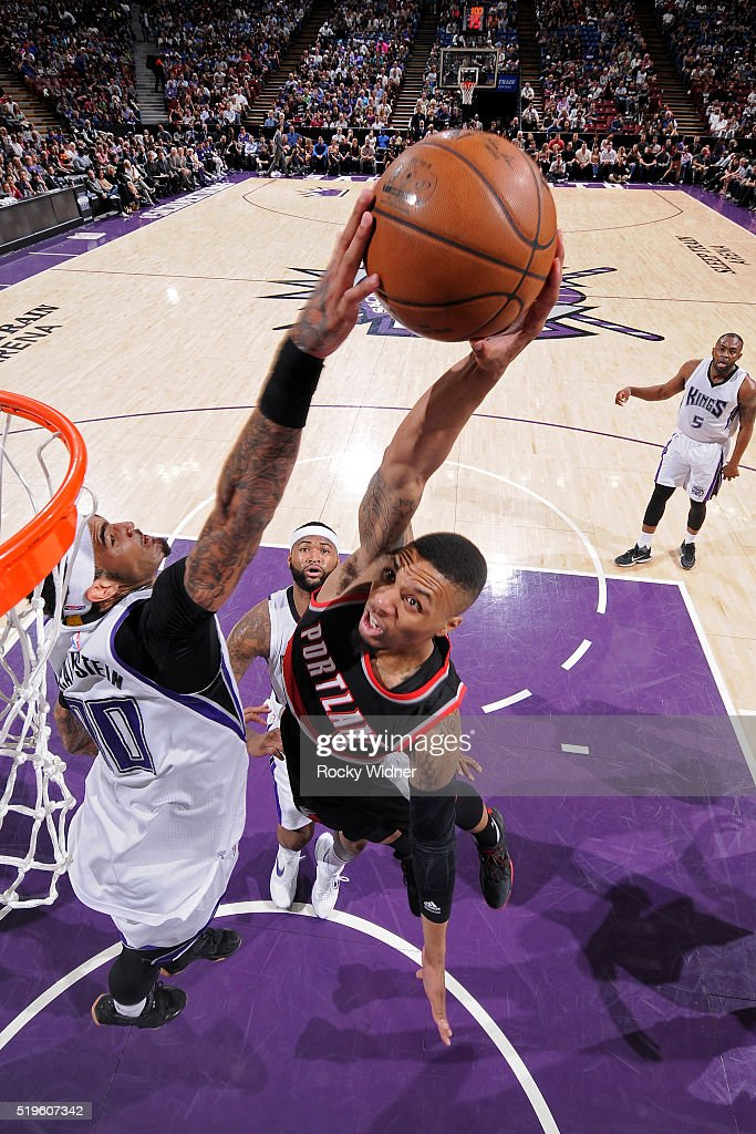 Damian Lillard of the Portland Trail Blazers dunks the ball while guarded by Willie CauleyStein of the Sacramento Kings at Sleep Train Arena on April...