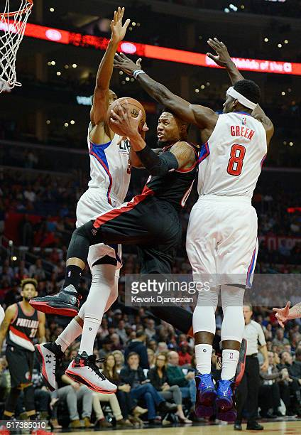 Damian Lillard of the Portland Trail Blazers glides through the defense off Wesley Johnson and Jeff Green of the Los Angeles Clippers during the...