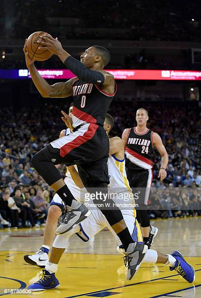 Damian Lillard of the Portland Trail Blazers goes up for a layup over Stephen Curry of the Golden State Warriors during an NBA basketball game at...