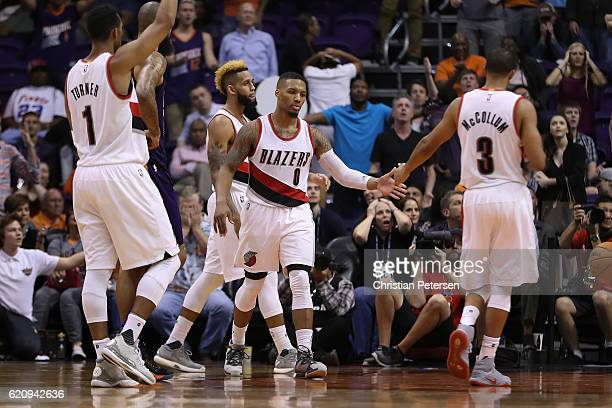 Damian Lillard of the Portland Trail Blazers high fives CJ McCollum and Evan Turner after scoring against the Phoenix Suns during overtime of the NBA...