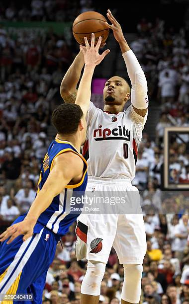 Damian Lillard of the Portland Trail Blazers hits a three point shot over Klay Thompson of the Golden State Warriors late in the fourth quarter of...