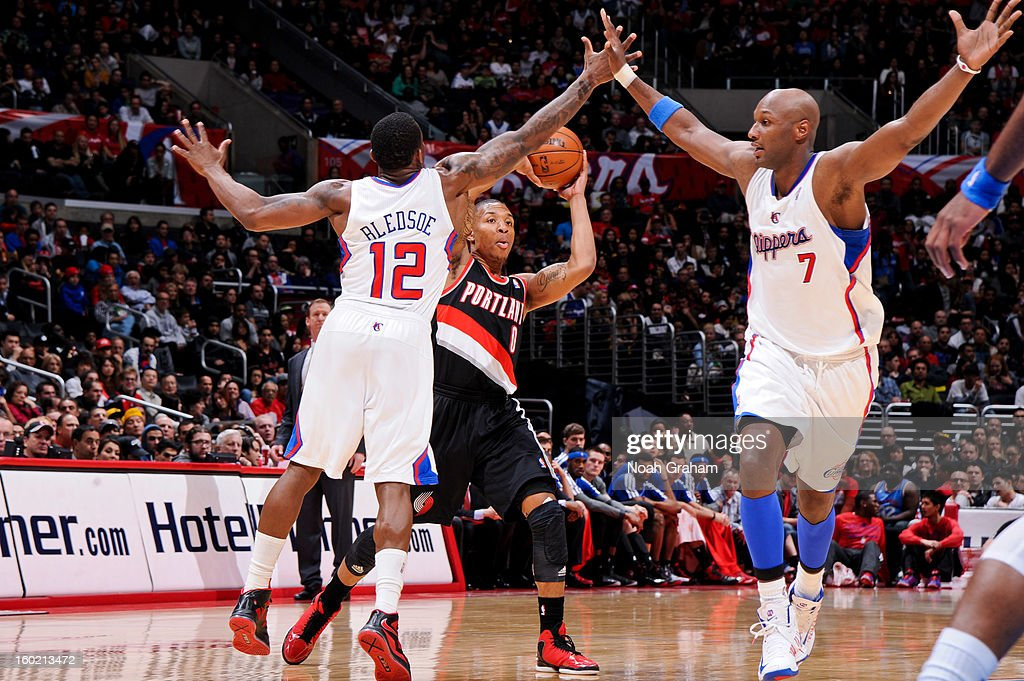 Damian Lillard #0 of the Portland Trail Blazers looks to pass the ball against Eric Bledsoe #12 and Lamar Odom #7 of the Los Angeles Clippers at Staples Center on January 27, 2013 in Los Angeles, California.