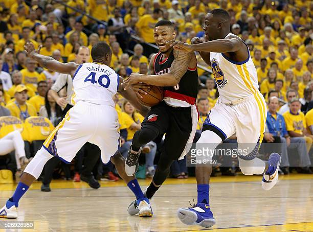 Damian Lillard of the Portland Trail Blazers tries to dribble between Harrison Barnes and Draymond Green of the Golden State Warriors during Game One...