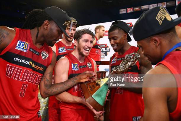 Damian Martin of the Wildcats celebrates with the trophy with Jameel McKay Angus Brandt Casey Prather and Bryce Cotton after winning game three and...