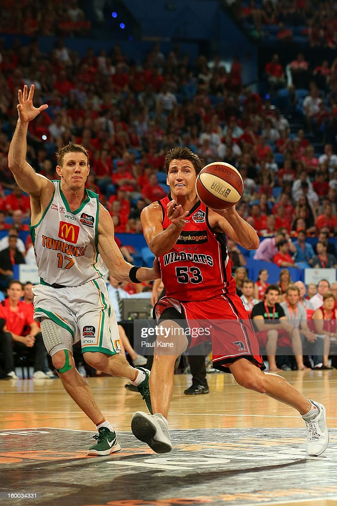 Damian Martin of the Wildcats passes the ball against Peter Crawford of the Crocodiles during the round 16 NBL match between the Perth Wildcats and the Townsville Crocodiles at Perth Arena on January 25, 2013 in Perth, Australia.