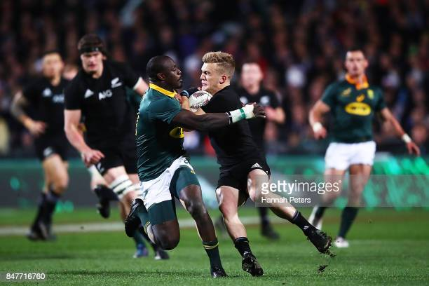 Damian McKenzie of the All Blacks charges forward during the Rugby Championship match between the New Zealand All Blacks and the South African...