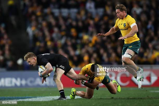 Damian McKenzie of the All Blacks is tackled by Curtis Rona of the Wallabies as Michael Hooper jumps in support during The Rugby Championship...