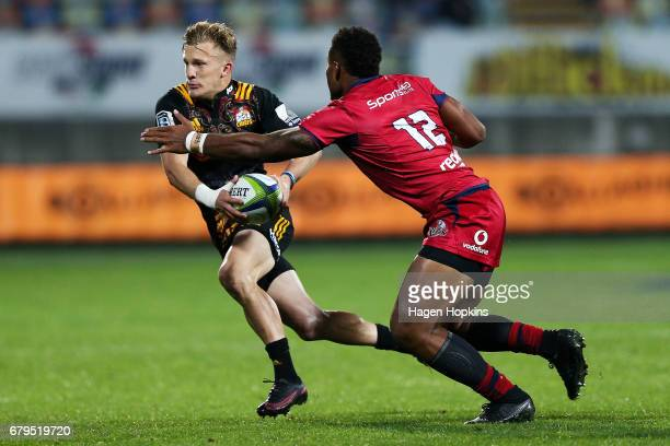 Damian McKenzie of the Chiefs attempts to beat the tackle of Samu Kerevi of the Reds during the round 11 Super Rugby match between the Chiefs and the...