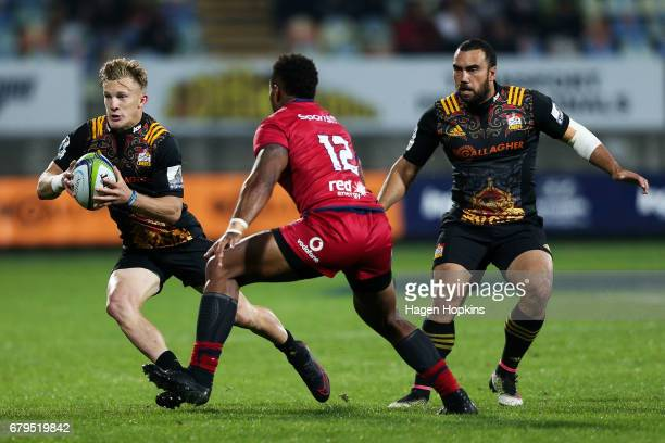 Damian McKenzie of the Chiefs attempts to beat the tackle of Samu Kerevi of the Reds while Charlie Ngatai looks on during the round 11 Super Rugby...