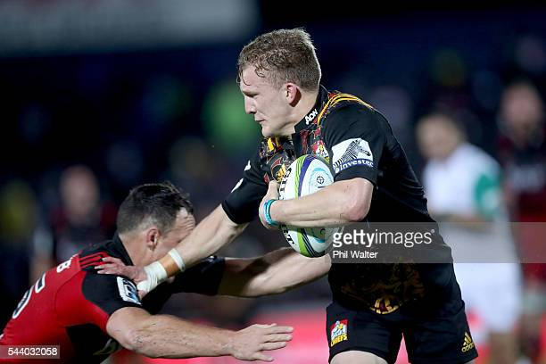 Damian McKenzie of the Chiefs fends off Israel Dagg of the Crusaders during the round 15 Super Rugby match between the Chiefs and the Crusaders at...