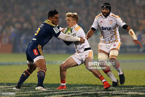 Damian McKenzie of the Chiefs fends off Malakai Fekitoa of the Highlanders during the round 16 Super Rugby match between the Highlanders and the...