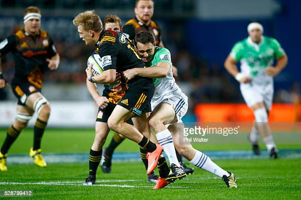 Damian McKenzie of the Chiefs is tackled by Ben Smith of the Highlanders during the round 11 Super Rugby match between the Chiefs and the Highlanders...