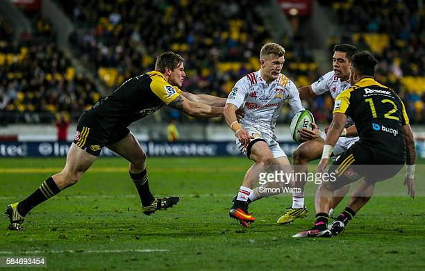 Damian McKenzie of the Chiefs looks to beat the tackle of Jason Woodward of the Hurricanes during the Super Rugby Semi Final match between the...