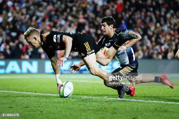 Damian McKenzie of the Chiefs scores a try against Tomas Cubelli of the Brumbies during the round 17 Super Rugby match between the Chiefs and the...