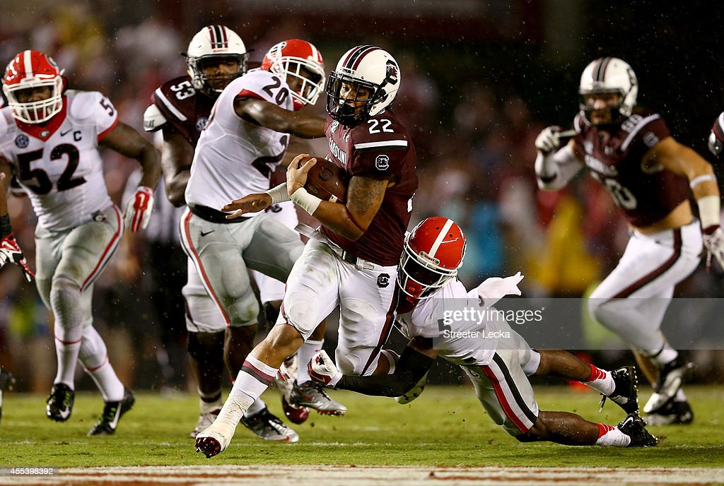 Damian Swann of the Georgia Bulldogs tries to stop Brandon Wilds of the South Carolina Gamecocks as he runs with the ball during their game at...