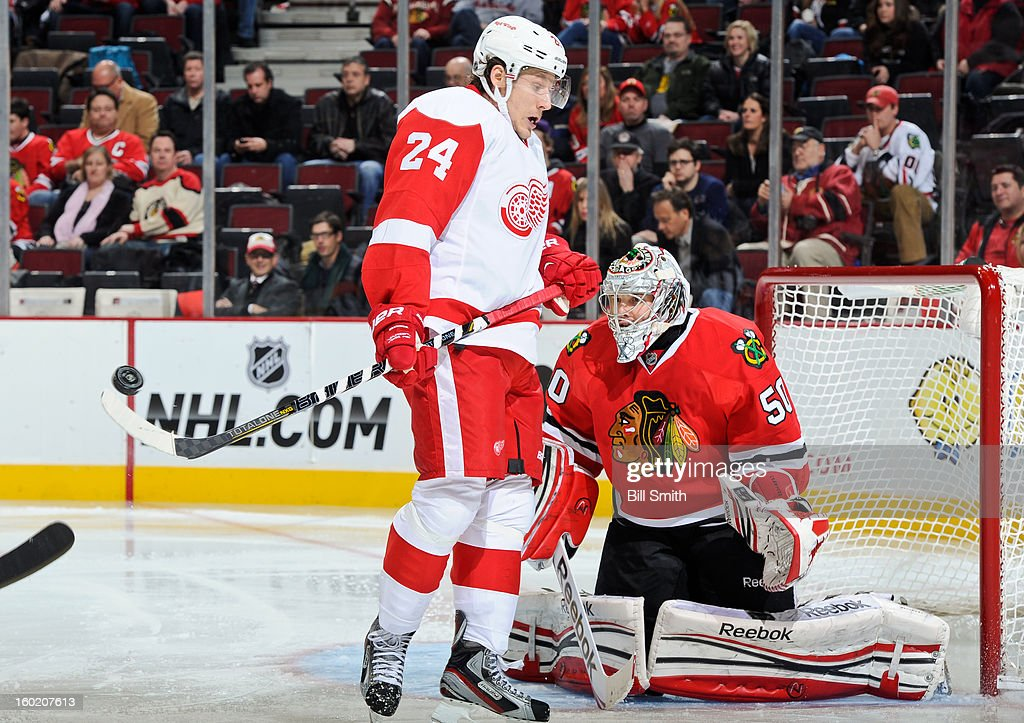 Damien Brunner #24 of the Detroit Red Wings is late to move out of the way of the puck in front of goalie <a gi-track='captionPersonalityLinkClicked' href=/galleries/search?phrase=Corey+Crawford&family=editorial&specificpeople=818935 ng-click='$event.stopPropagation()'>Corey Crawford</a> #50 of the Chicago Blackhawks during the NHL game on January 27, 2013 at the United Center in Chicago, Illinois.