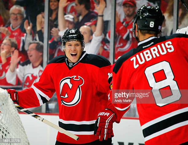 Damien Brunner of the New Jersey Devils celebrates with teammate Dainus Zubrus after scoring his first goal of the season during the Devils home...