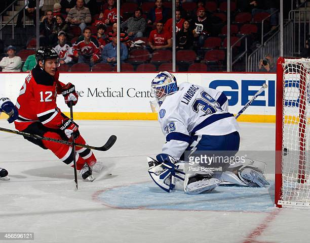 Damien Brunner of the New Jersey Devils shoots the puck past goalie Anders Lindback of the Tampa Bay Lightning for the first goal of the game during...
