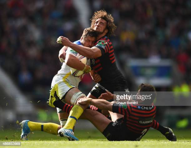 Damien Chouly of ASM Clermont Auvergne is tackled by Jacques Burger and Schalk Brits of Saracens during the Heineken Cup SemiFinal match between...
