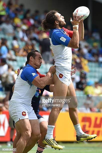 Damien Cler of France lifts his teammate Jonathan Laugel during their Bowl quarterfinal game at the Sydney Sevens rugby union tournament in Sydney on...