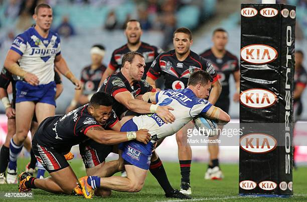Damien Cook of the Bulldogs scores a try during the round 26 NRL match between the Canterbury Bulldogs and the New Zealand Warriors at ANZ Stadium on...