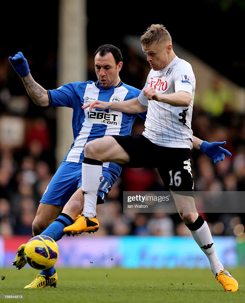 Damien Duff of Fulham is challenged by Ivan Ramis of Wigan during the Barclays Premier League match between Fulham and Wigan Athletic at Craven...