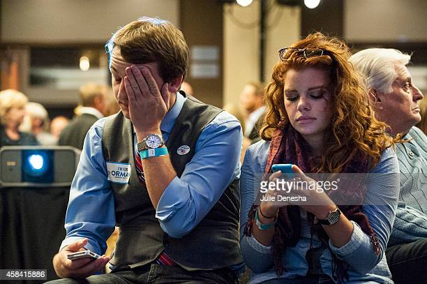 Damien Gilbert and Alexis Simmons of Wichita Kansas watch their phones to follow election results at a watch party on election night for Independent...