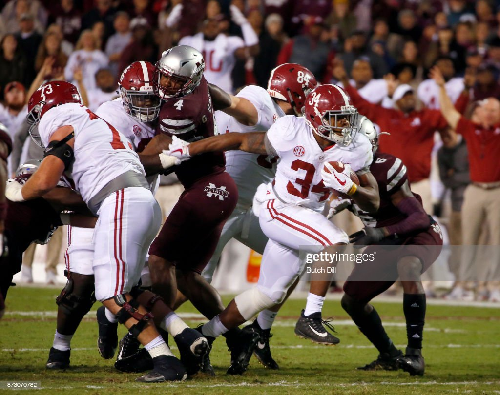 Damien Harris #34 of the Alabama Crimson Tide breaks through the line and carries the ball in for a touchdown during the second half of an NCAA football game against the Mississippi State Bulldogs at Davis Wade Stadium on November 11, 2017 in Starkville, Mississippi.
