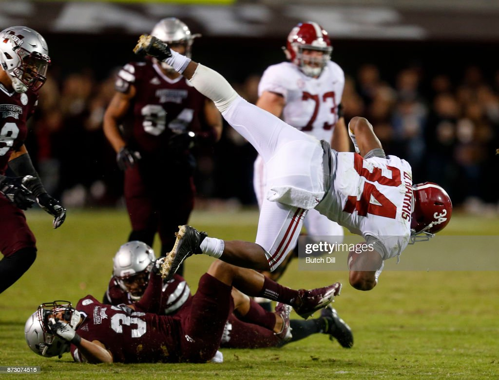 Damien Harris #34 of the Alabama Crimson Tide flips over Johnathan Abram #38 of the Mississippi State Bulldogs as he carries the ball during the second half of an NCAA football game at Davis Wade Stadium on November 11, 2017 in Starkville, Mississippi.