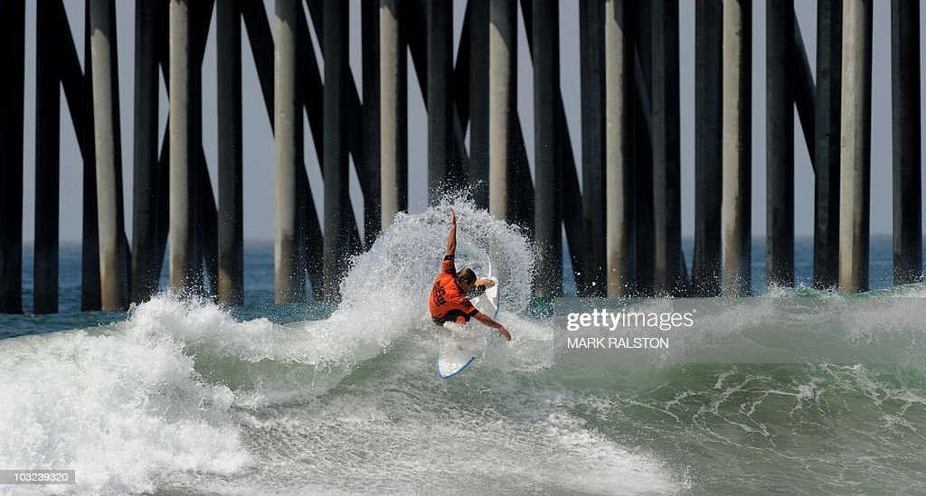 Damien Hobgood of the US does a cutback close to the pier as he competes in his heat during the US Open of Surfing at Huntington Beach California on...