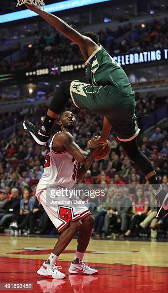 Damien Inglis of the Milwaukee Bucks leaps over E'Twaun Moore of the Chicago Bulls during a preseason game at the United Center on October 6 2015 in...