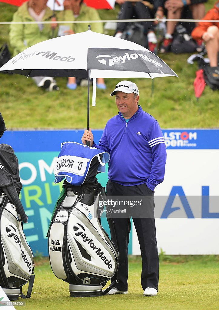 Damien McGrane of Ireland plays shelters under an Umbrella on the 1st tee during the Alstom Open de France - Day Four at Le Golf National on July 6, 2014 in Paris, France.