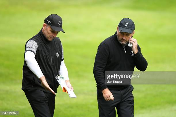 Damien McGrane of the Great Britain and Ireland PGA Cup team chats with partner David Higgins during the afternoon foursomes matches on day 2 of the...