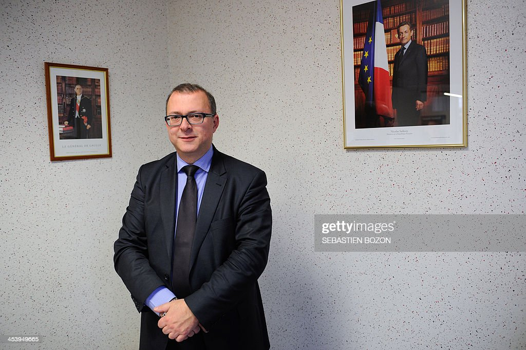 Damien Meslot, UMP right-wing party candidate for the 2014 municipal elections in Belfort, eastern France, poses on December 6, 2013 in front of two pictures representing Formers French President Charles De Gaulle (L) and Nicolas Sarkozy. AFP PHOTO / SEBASTIEN BOZON