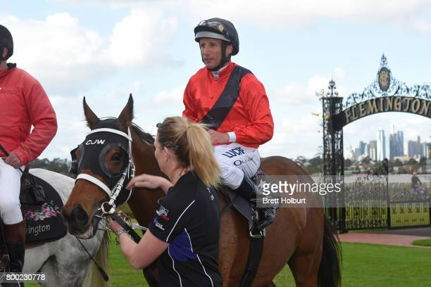 Damien Oliver returns to the mounting yard on Encosta Line after winning Grampians Region Handicap at Flemington Racecourse on June 24 2017 in...